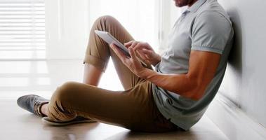 hombre guapo con tableta sentado en el suelo