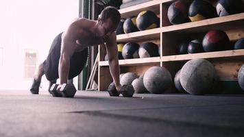 Un jeune homme en forme faisant des pompes avec des haltères dans une salle de sport