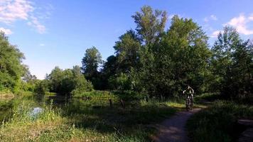 Junge Teenager fährt ein Sportfahrrad. Junge reitet im Park. alter Park am Abend.