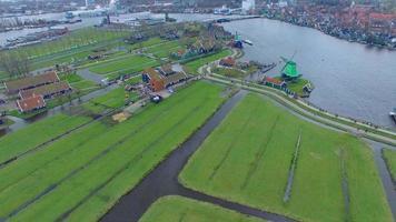 Países Bajos pueblo de molinos de viento, campo elevado con vistas a casas y molinos de viento