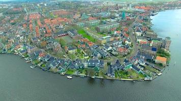Países Bajos aldea de molinos de viento volar hacia edificios frente al agua