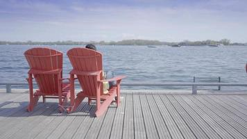 homens relaxando em uma cadeira canadense olhando para o lago no porto de toronto video