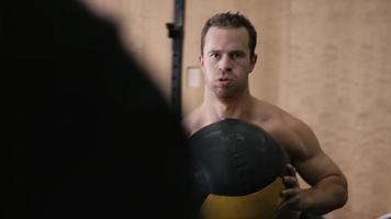 um jovem em forma correndo e passando uma bola de medicina em um pequeno ginásio