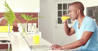 uomo sorridente casuale che beve succo d'arancia