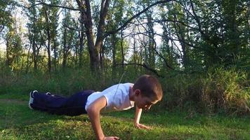 Der schlanke Teenager wird im Wald aus dem Boden gerungen. Junge ist trainiert, stärker zu werden. Sport in der Natur.