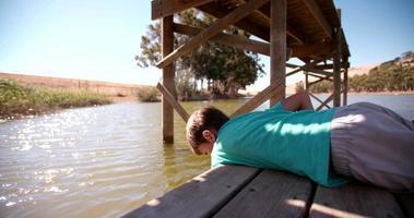 ragazzo sdraiato su un molo che gioca con l'acqua