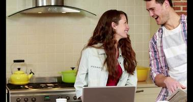 pareja sonriente discutiendo sobre una tableta