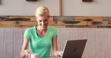 bella bionda usando il suo laptop e bevendo caffè