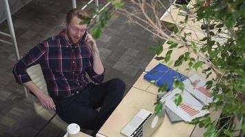 imponente uomo barbuto seduto su una sedia e parlando al telefono