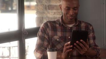 uomo che utilizza un tablet per chattare video in un caffè
