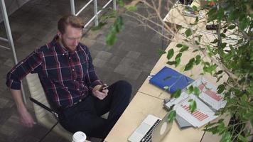 um homem barbudo com um sorriso malicioso no rosto olhando para o smartphone video