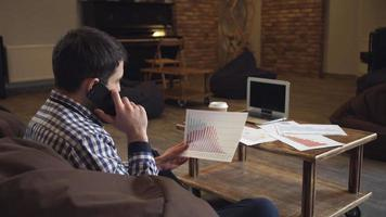un uomo con una camicia che tiene in mano un grafico e parla al telefono