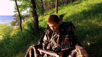 ragazzo adolescente seduto su una sedia sulla riva di un grande lago. ragazzo adolescente con entusiasmo giocando a un gioco per computer su un tablet pc