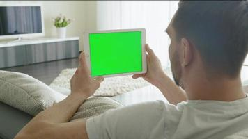 Man is Laying on Couch at Home and Watch on Tablet with Green Screen in Landscape Mode. video