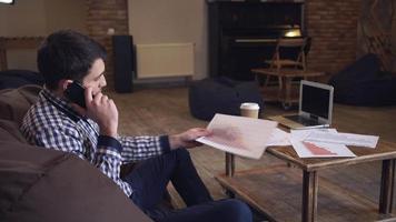 Manager telefoniert in einem Sessel, ein Laptop liegt auf dem Tisch