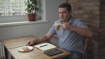 homem adulto com uma camisa azul pela manhã sentado em um café, bebendo café e comendo torradas, está na mesa e no tablet diariamente video
