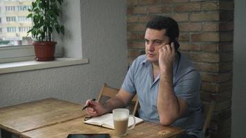 homem adulto atraente descansando em um café e falando ao telefone video