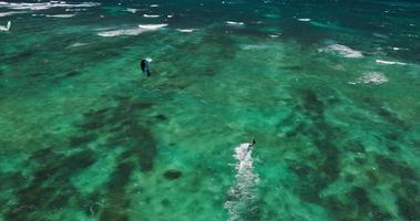 vista aérea de kitesurfista deslizando pelo oceano azul