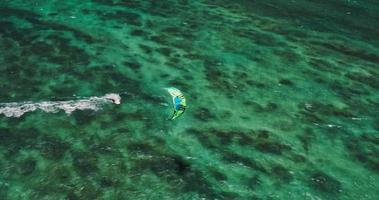Aerial view of kitesurfer gliding across blue ocean