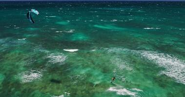 Vista aérea del kitesurfer deslizándose por el océano azul