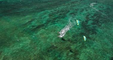 Aerial view of kitesurfers gliding across blue ocean