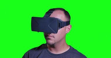 A man in a virtual reality mask looks around and manipulates his surroundings.
