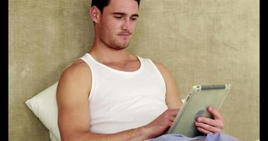uomo che si distende nel suo letto utilizzando tablet pc