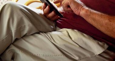 Senior man using tablet pc alors qu'il était assis dans un fauteuil à bascule