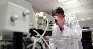 jonge wetenschapsstudent die door een krachtige microscoop kijkt
