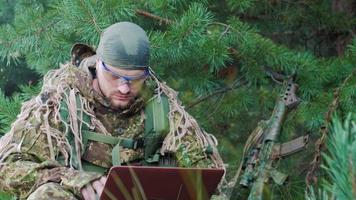 Porträt eines Militärs, der im Wald sitzt, in Tarnung gekleidet. Es verwendet Laptop