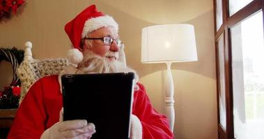 Babbo Natale guardando attraverso la finestra mentre si utilizza la tavoletta digitale video