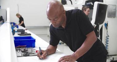 engenheiro fazendo anotações no desenho técnico na fábrica video