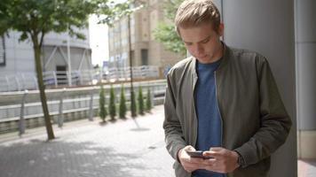 giovane uomo bianco di messaggistica con lo smartphone nel contesto urbano