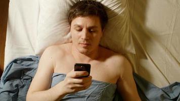 Tipos de joven caucásico por teléfono móvil en una cama