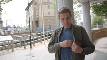 giovane uomo bianco che cammina nel contesto urbano rispondendo al suo telefono