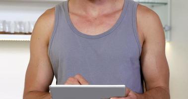 een glimlachende man met een tanktop met zijn digitale tablet