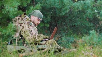 uomini armati in tuta mimetica seduti nei boschi. usa laptop. vista laterale