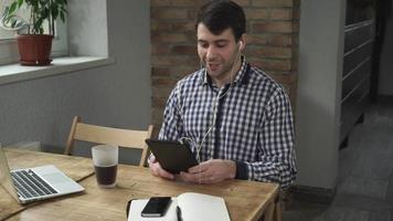 o homem está sentado a uma mesa com um tablet, fones de ouvido, conversando online video