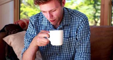 apuesto joven relajante tomando café video