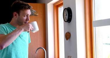 apuesto joven tomando café mirando por la ventana video
