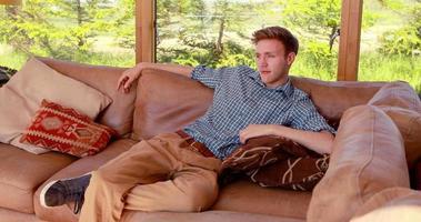 bel giovane rilassante sul suo divano video