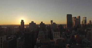 absteigender Schuss während des Sonnenuntergangs, der die Illusion der Sonne erzeugt, die sich hinter dem Gebäude versteckt