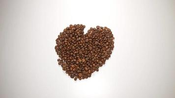 TOP VIEW: Love symbol from a coffee beans on a white table (stop motion) video