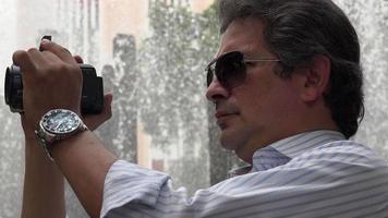 turista alla fontana con la macchina fotografica video