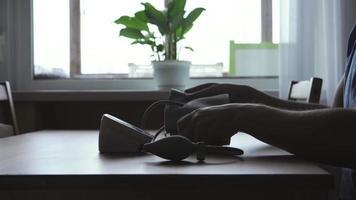 una silhouette di un giovane uomo che misura la pressione sanguigna a casa vicino alla finestra