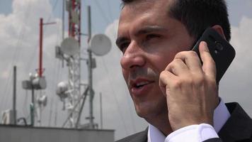 homem falando ao telefone perto da torre de celular video