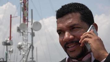 homem falando no celular perto da torre de celular video