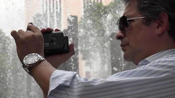 turista na fonte com câmera video