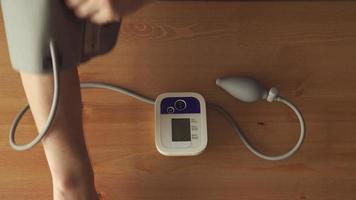 top view-close up: mani di un giovane che misura la pressione sanguigna al tavolo