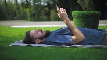 Mann, der mit Smartphone an der frischen Luft ruht